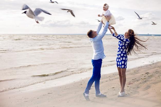 Felice giovane coppia solleva nelle mani di una bambina sulla spiaggia. la ragazza con il vestito blu, camicia ragazzo in stile marinaro. gabbiani che volano intorno