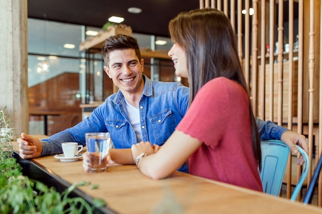 Felice giovane coppia al ristorante in attesa di cibo e parlare