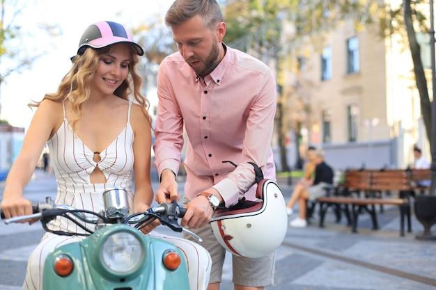 Felice giovane coppia in sella a uno scooter in città. bel ragazzo e giovane donna viaggiano. concetto di avventura e vacanze.