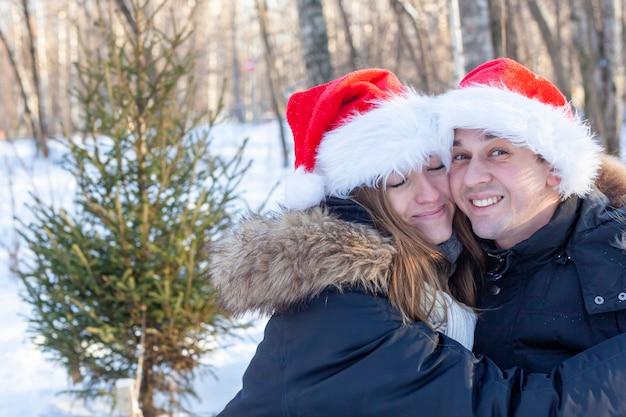 La giovane coppia felice in cappelli di babbo natale sorride e ride sullo sfondo di una foresta invernale con un albero di natale.