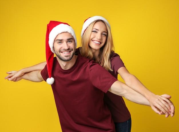 Felice giovane coppia in cappelli di babbo natale su giallo