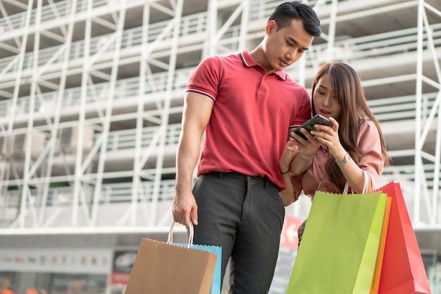 Giovani coppie felici di clienti che camminano nella strada dei negozi verso