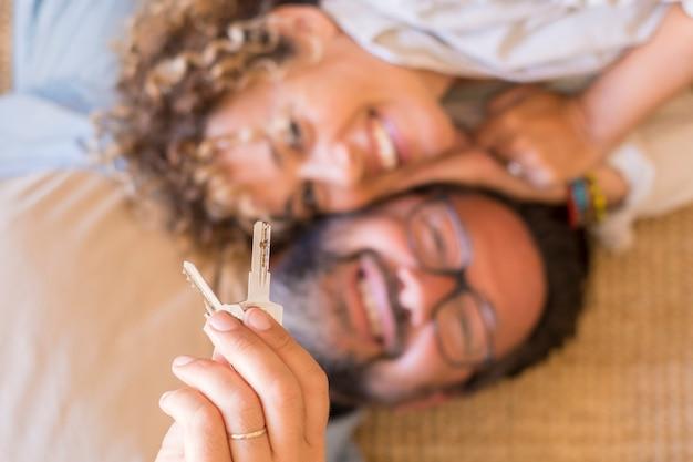 Felice giovane coppia mostra le nuove chiavi di casa entusiasta di trasferirsi insieme, sorridente amorevole marito e moglie adulti felicissimi per la prima volta che gli acquirenti si trasferiscono in un appartamento condiviso in affitto