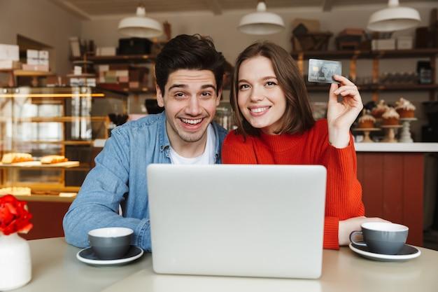 Giovani coppie felici che mostrano la carta di credito