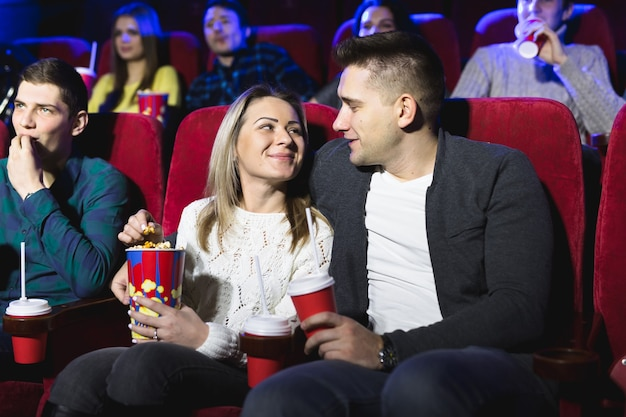 Felice giovane coppia seduta al cinema e si diverte a guardare il film