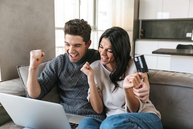 Felice giovane coppia seduta su un divano a casa, utilizzando il computer portatile