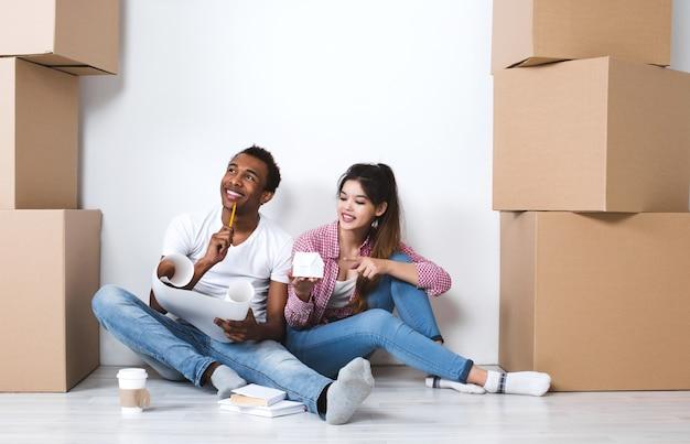 Giovani coppie felici che si siedono sul pavimento che sogna di una nuova casa. in movimento.