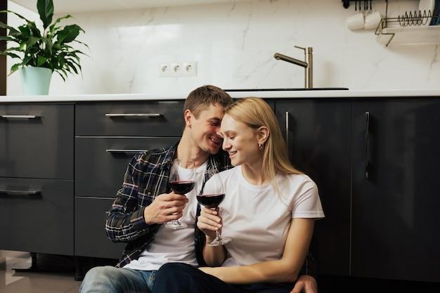 Felice giovane coppia seduta sul pavimento in cucina e bere vino rosso.