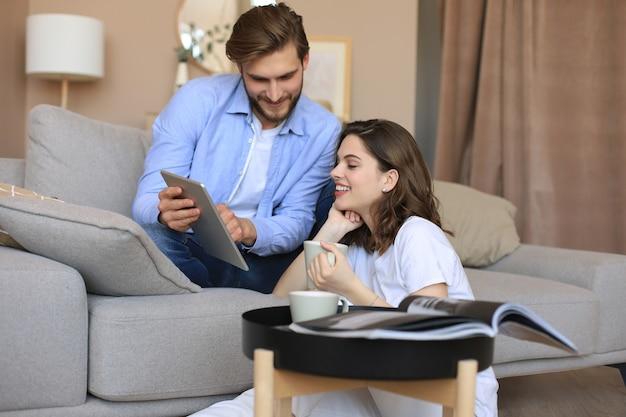 Felice giovane coppia seduta, rilassante sul pavimento in soggiorno a guardare contenuti multimediali online, fare shopping online in un tablet.