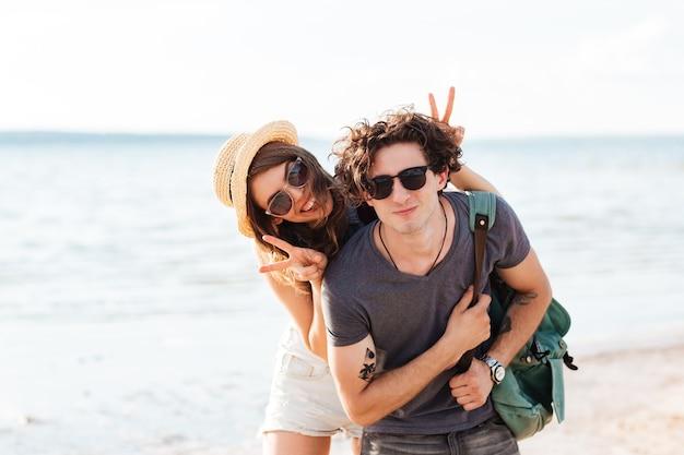 Giovani coppie felici che sorridono e che si divertono insieme sulla spiaggia