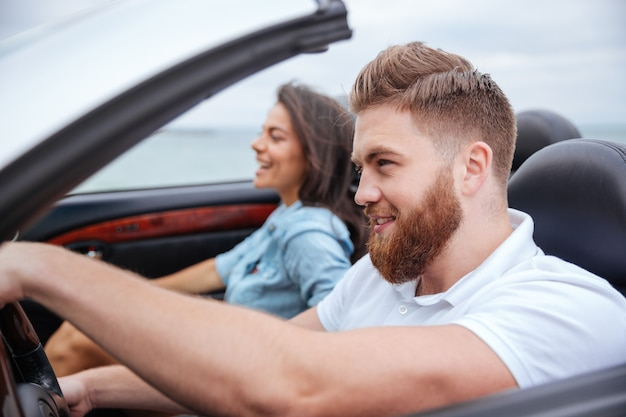 Felice giovane coppia sorridente mentre era seduto all'interno della loro decappottabile