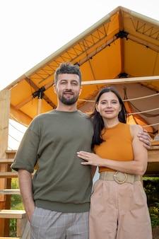 Felice coppia giovane in piedi contro la tenda glamping