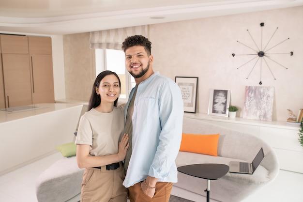 Felice giovane coppia in piedi davanti alla telecamera in soggiorno