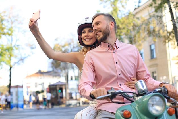 Felice coppia giovane prendendo selfie su smartphone mentre è seduto su uno scooter all'aperto.
