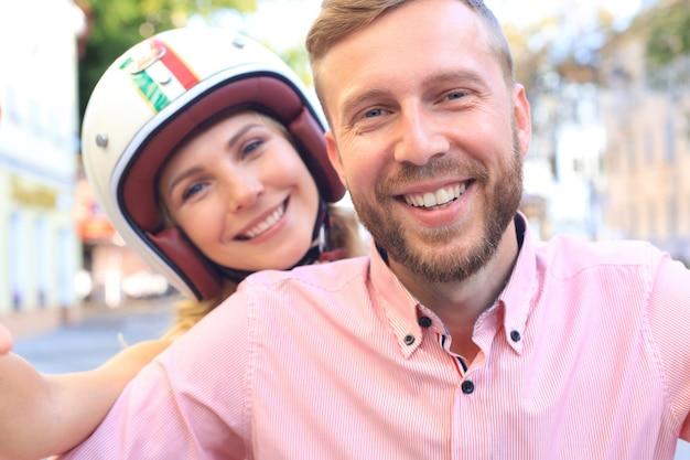 Felice coppia giovane prendendo selfie seduti su uno scooter all'aperto.