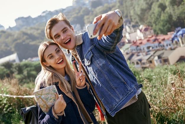 La giovane coppia felice dei turisti prende il ritratto del selfie sul paese europeo