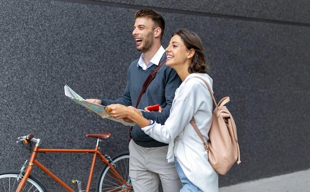 Felice giovane coppia di viaggiatori che tengono la mappa in mano all'aperto