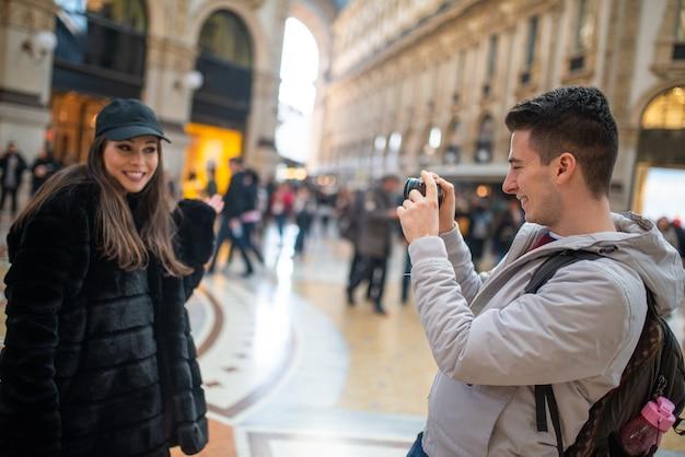 Felice giovane coppia di turisti a scattare foto a milano, italy