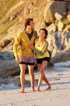 Giovani coppie felici che camminano insieme sulla spiaggia