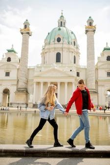 Giovani coppie felici che camminano dalla chiesa cattolica di san pietro a vienna, austria