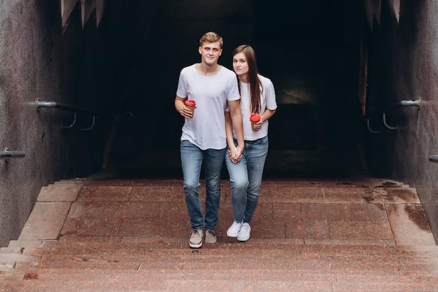 Felice giovane coppia cammina per le strade della città e beve il caffè da una tazza di cartone.