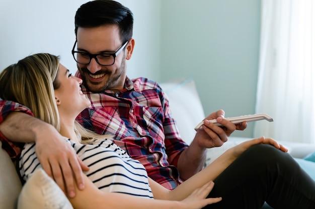 Giovani coppie felici che guardano la tv a casa loro