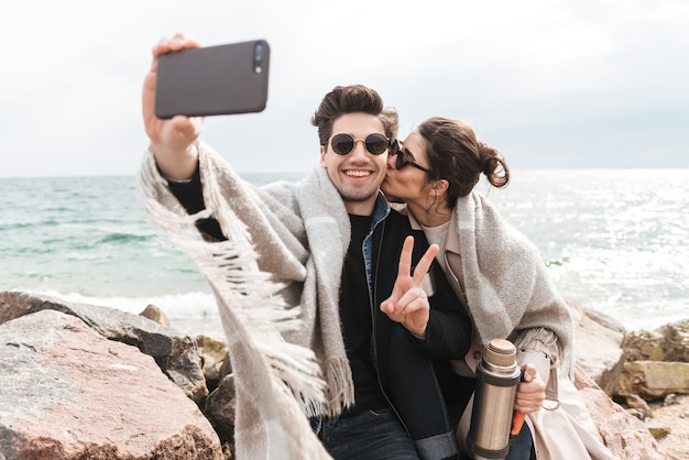 Felice giovane coppia che indossa cappotti autunnali trascorrono del tempo insieme al mare, seduti coperti in una coperta, bevendo caffè dal thermos, facendo un selfie