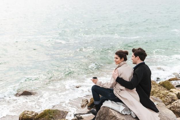 Felice coppia giovane che indossa cappotti autunnali trascorrono del tempo insieme al mare, seduti coperti da una coperta