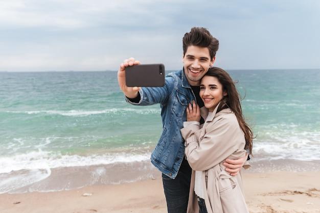 Felice giovane coppia che indossa cappotti autunnali trascorrono del tempo insieme al mare, facendo un selfie
