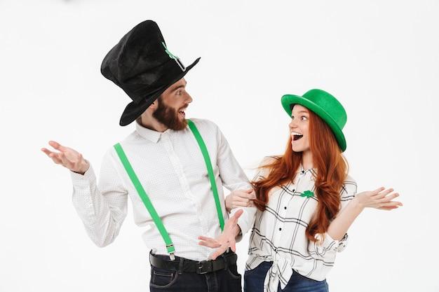 Giovani coppie felici che indossano costumi, celebrando il giorno di stpatrick isolato sopra il muro bianco, divertendosi insieme