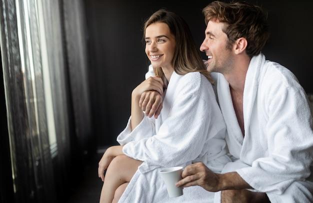 Felice giovane coppia in accappatoi bianchi che bevono caffè insieme al mattino