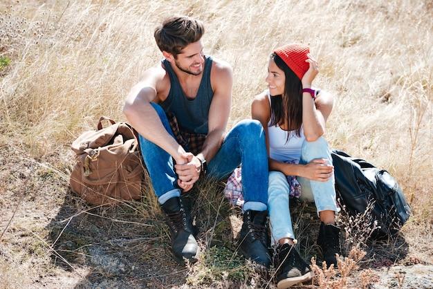 Giovani coppie felici con gli zaini che hanno un campo all'aperto