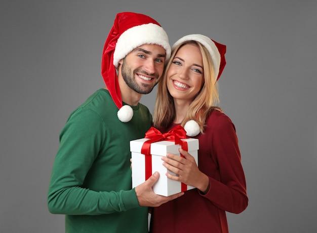Felice giovane coppia con regalo di natale sulla superficie grigia