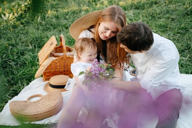 Felice giovane coppia con figlia in una passeggiata in un parco estivo sedersi solleticare e giocare con un bambino