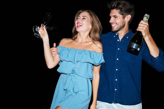 Felice giovane coppia con bicchieri e bottiglia di champagne sulla spiaggia di notte