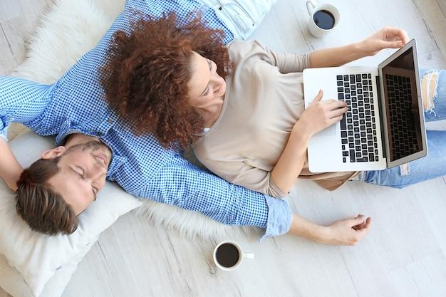 Giovani coppie felici con il computer portatile a casa
