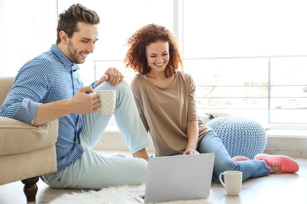 Felice giovane coppia con laptop a casa at