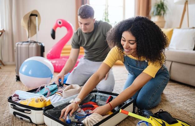 Felice giovane coppia con imballaggio portatile per le vacanze estive, concetto di coronavirus.
