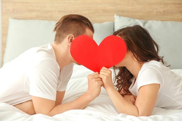 Felice giovane coppia con cuore di carta sdraiata a letto Foto Premium
