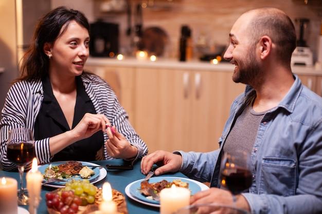 Felice giovane coppia con notizie sulla gravidanza durante una cena romantica, coppia eccitata che sorride, ar per questa grande notizia. incinta, giovane moglie felice per il risultato che abbraccia l'uomo.