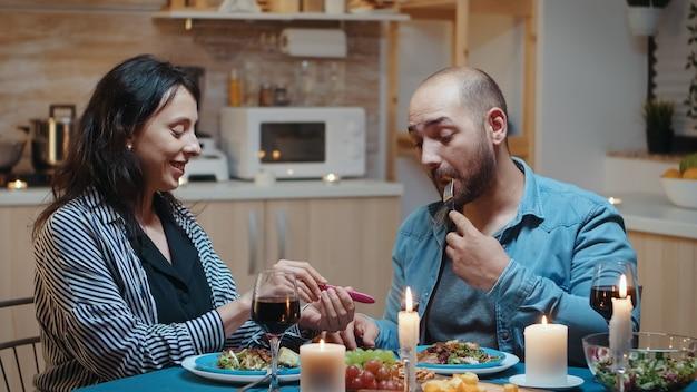 Felice giovane coppia con notizie sulla gravidanza durante una cena romantica, seduta in cucina. coppia eccitata che sorride, si abbraccia e si bacia per risultati positivi. moglie incinta che abbraccia l'uomo.