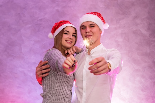 Felice giovane coppia con cappello da babbo natale e le stelle filanti di natale girato in studio.