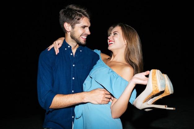 Felice giovane coppia con le scarpe in mano che si abbraccia e ride di notte