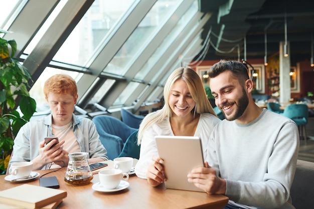 Giovani coppie felici con il touchpad che parlano tramite chat video o guardano film online mentre ci si rilassa nella caffetteria con il loro amico