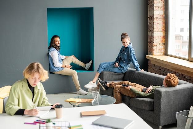Felici giovani designer creativi in abbigliamento casual seduti vicino alla finestra in ufficio, brainstorming e discutendo i punti di lavoro alla riunione