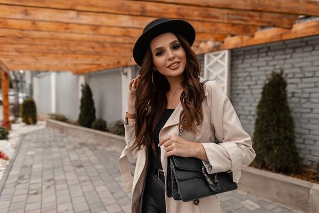 Felice giovane ragazza bruna dai capelli ricci con un sorriso in abiti alla moda con un cappello vintage e una borsa in pelle cammina per strada. elegante stile e bellezza femminile autunnale