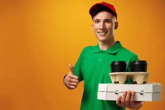 Felice giovane fattorino che tiene la scatola della pizza contro la superficie gialla