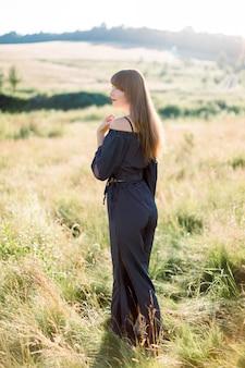 Felice giovane donna dai capelli scura elegante in vestiti neri, godersi la natura, in posa nel campo verde bella estate al tramonto