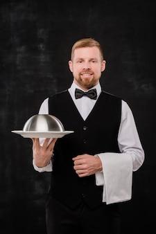 Felice giovane cameriere elegante che tiene asciugamano bianco e cloche con il cibo mentre ti guarda su sfondo nero