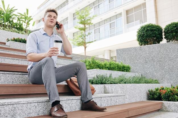 Felice giovane imprenditore seduto sui gradini, bevendo caffè da asporto e chiamando il telefono